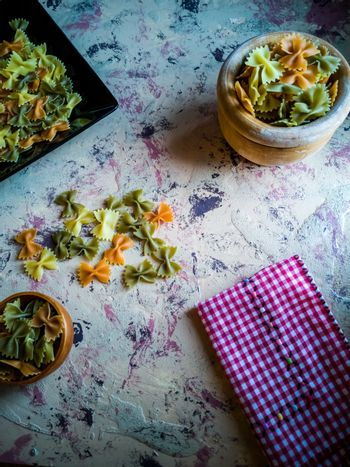 Colorful pasta ties in composition on light and rough background
