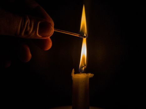 Matches burning to light a candle on black background