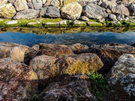 Rocks reflected in the water on the beach