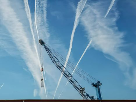 View of blue crane with sky with contrails of aircraft