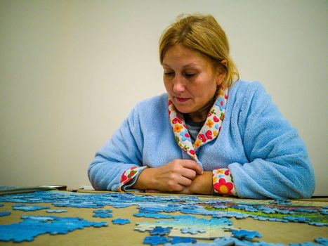 Woman in lab coat making puzzle at home
