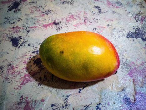 Ariel view of tropical mango on a rough background in purple tones