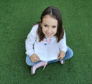 Smiling girl reading sitting on artificial grass