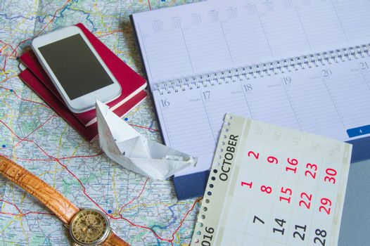 Diary and calendar with clock, passport, card, paper boat, travel concept with copy space.