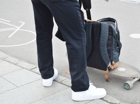 Skateboarder puts things in his backpack with the skateboard. The concept of sports lifestyle.