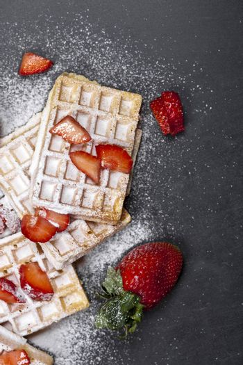 Belgium waffers with strawberries and sugar powder on black board background.