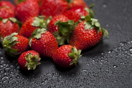 Fresh ripe strawberry with water drops closeup on black background.
