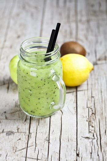 Green smoothie with kiwi, apple, lemon and chia seeds. Healthy fresh diet eating, superfood on wooden rustic background.