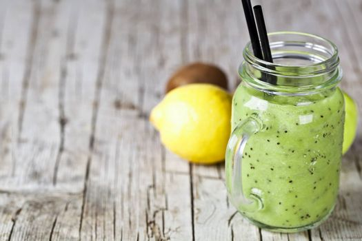Green smoothie with kiwi, apple, lemon and chia seeds. Healthy fresh diet eating, superfood on wooden rustic background with copy space.