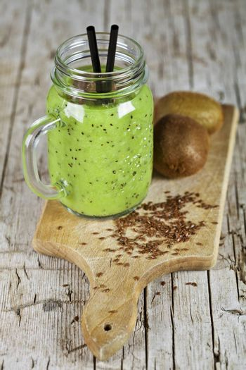 Green smoothie with kiwi, apple, lemon and linen seeds. Healthy fresh diet eating, superfood on wooden rustic background.