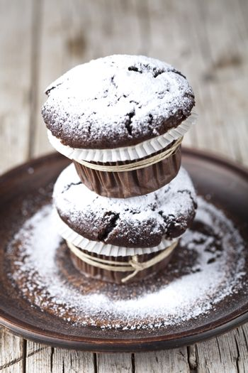 Chocolate dark muffins with sugar powder on brown plate on rustic wooden table background.