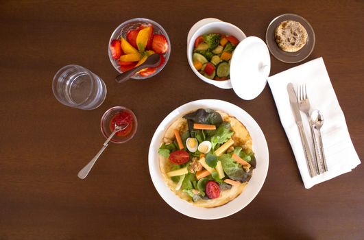 Full healthy menu composed of salad, chicken with vegetables, bread and fruit salad