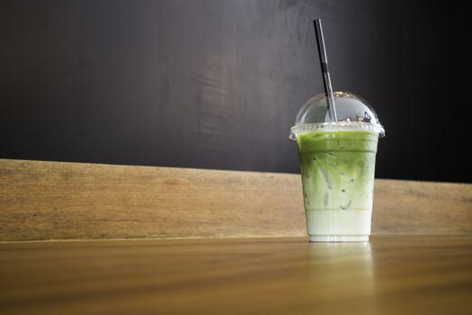 Iced green tea latte on wooden table, stock photo