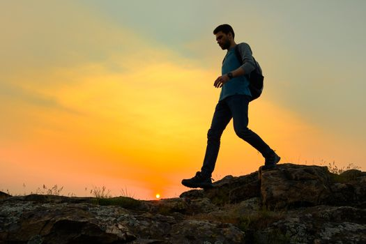 Young Happy Man Traveler Hiking with Backpack on the Rocky Trail at Warm Summer Sunset. Travel and Adventure Concept.