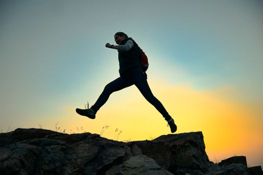 Young Woman Traveler Jumping with Backpack on the Rocky Trail at Warm Summer Sunset. Travel and Adventure Concept.