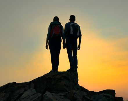 Couple of Young Travelers with Backpack Standing on the Top of the Rock at Summer Sunset. Travel and Adventure Concept.