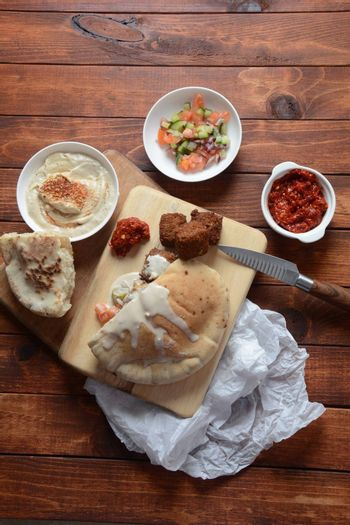 Falafel in pita bread with vegetable salad, harissa sauce, humus, tahini on wooden background. Traditional Israeli food. Middle eastern fast food concept