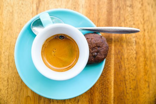 An espresso served with a chocolate cookie in a turquoise cup on a wood table