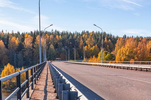 Highway bridge over the river with a metal fence in the fall