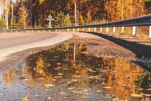 Highway over the bridge over the river with a metal fence in the fall, in the distance is a worship cross. Dangerous driving concept