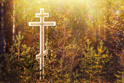 Orthodox worship cross in the forest on the side of the road at the entrance of the village in autumn