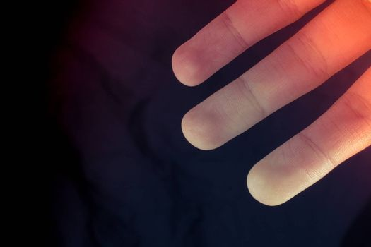 Three fingers of a child hand partly seen in black background