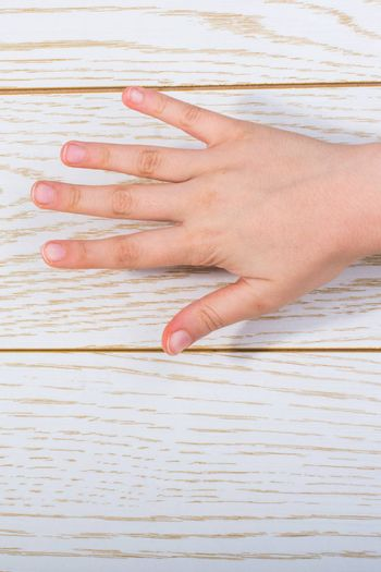Hand making a gesture on a wooden background