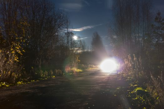 Bright headlights of the oncoming car on the night road