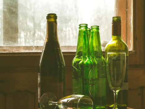 Several empty bottles of alcohol near the dirty window. Selective focus. Alcoholism, drunkenness, loneliness and depression concept