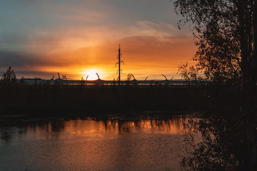 Highway and power lines on sunset background, view from the riverbank