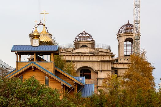 Small wooden church with a blue roof and gilded domes on the background of a large temple