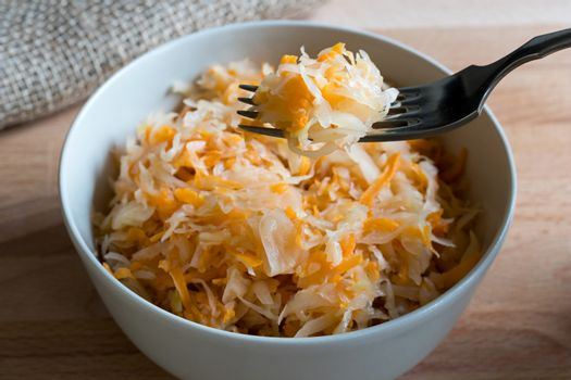 Fermented cabbage and carrots in a bowl and on a fork