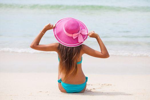 Travel woman on beach enjoying blue sea and sky wearing pink beach sun hat and bikini