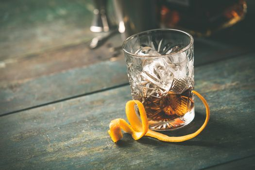 Alcoholic cocktail  with orange peel and ice