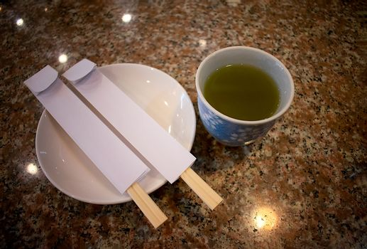 Cup of Green Tea and Two pairs of Displosable Chopsticks on a Marble Table