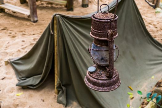 old rusty lantern with a tent in the background, the Miners camp, survival hike in nature
