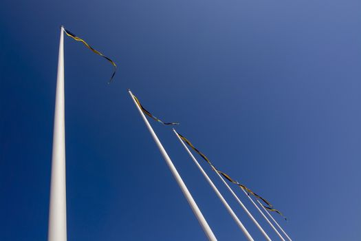 Swedish flagpoles in a diagonal row with blue and yellow pennants on a sunny day against blue sky.
