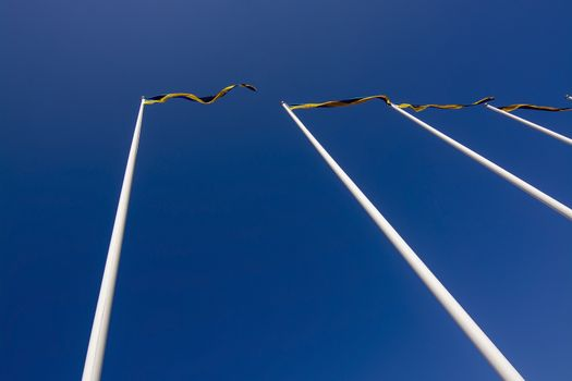 Swedish flagpoles in a row with blue and yellow pennants on a sunny day against blue sky.