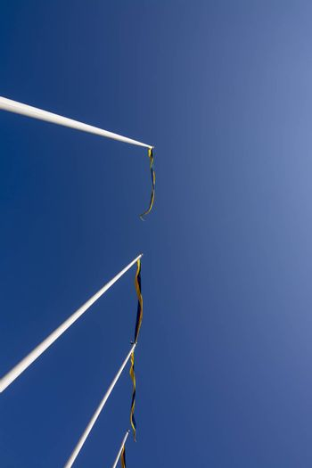 Swedish flagpoles in a vertical row with blue and yellow pennants on a sunny day against blue sky.