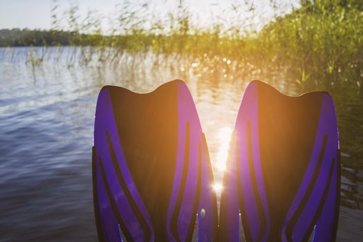 legs in flippers by the lake on a hot summer day
