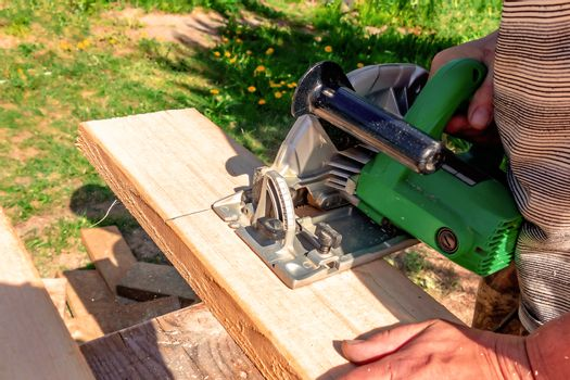 A man is sawing a board with a circular saw in the open air