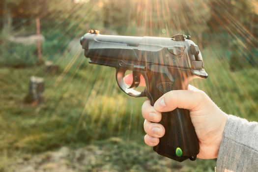 Female hand with pneumatic gun, outdoors close-up