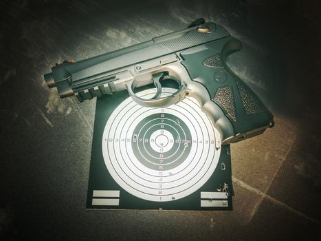 Pneumatic pistol and target with shooting results in dramatic light, as if hit