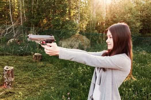 Pretty young Girl aiming from a pneumatic gun, outdoors