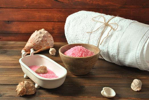 Spa and body care products. Aromatic rose bath Dead Sea Salt on the dark wooden background. Natural ingredients for homemade body salt scrub. Dead Sea cosmetics. Beauty skin care. Spa treatment.