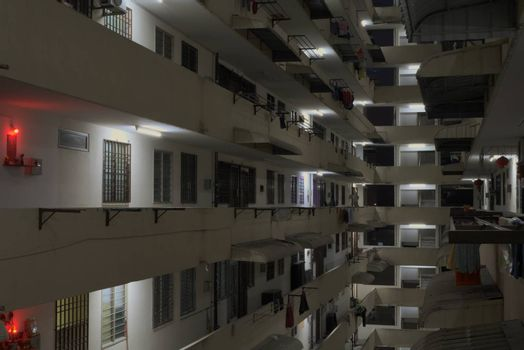 inside housing complex block with hanging clothes and red lights