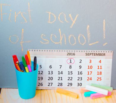 First day at school writing on the blackboard, calendar, stationery.