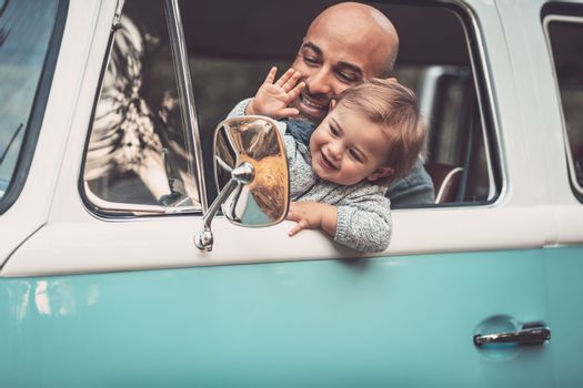 Happy family in the car, summer travel in the van, cheerful father with his adorable little son driving wagon, smiling and waving his hands, enjoying parenthood