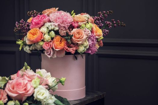 Bouquet of different beauty flowers in round present box on dark background
