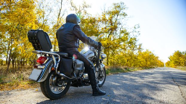 Motorcycle Driver Riding Custom Chopper Bike on Autumn Road. Travel and Adventure Concept.